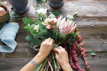 Cvjećarica na poslu: prilično mlada plavokosa žena izrađuje modni moderni buket od različitog cvijeća