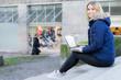 studentin sitzt mit dem laptop auf einer treppe