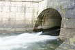 Nebliges Wasser fliesst durch den Tunnel in den Fluss Bach