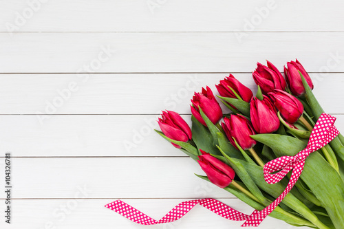 obraz lub plakat Red tulips bouquet decorated with ribbon. Copy space