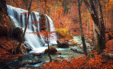 FototapetaBeautiful waterfall at mountain river in colorful autumn forest with red and orange leaves at sunset. Nature landscape