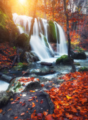 Fototapeta Vintage Beautiful waterfall at mountain river in colorful autumn forest with red and orange leaves at sunset. Nature landscape