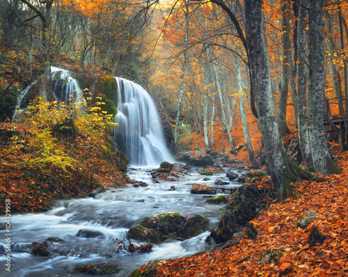 Poster Bordeaux Beautiful waterfall at mountain river in colorful autumn forest with red and orange leaves at sunset. Nature landscape