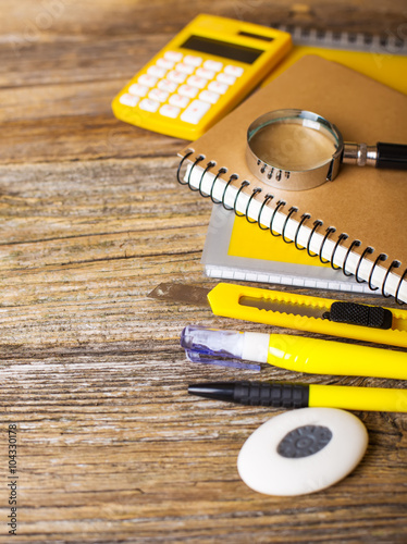 School supplies of yellow color on a wooden background - 104330178