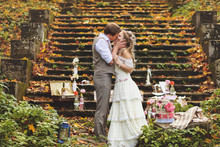 Wedding Couple In A Rustic Style Kissing Near The Stone Steps Surrounded By Wedding Decor