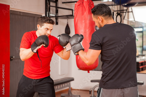 Young men sparring in boxing room - 104343332