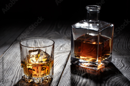 Fotografiet  Backlit glass of whiskey with ice