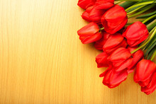 Red Tulips On A Wooden Background