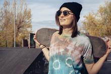 Smiling Young Woman Holding Skateboard At Skatepark