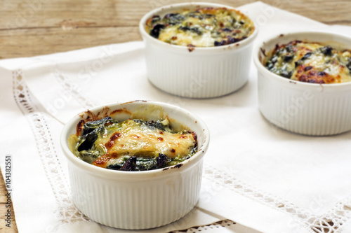 Stickers pour porte Entree baked spinach with cheese in small casserole servings, white nap