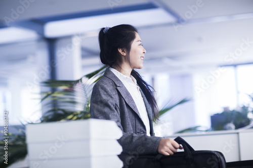 Young Chinese woman with briefcase in office