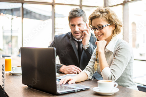 Two business partners sitting in a coffee shop looking at laptop