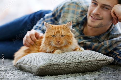 Spoed Foto op Canvas Canada Young man with fluffy cat lying on a carpet