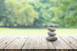 zen stones on wooden in the garden. vintage wood table in relaxing wellness holistic spa for relaxation and good health rejuvenation. stones stacked on wooden table outdoors.