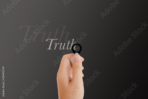 Fotografia  Isolated hand with lens and text truth on dark platinum backgrou