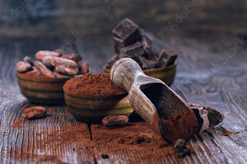 Aluminium Prints Candy Dark chocolate pieces, cocoa powder and cocoa beans on a wooden table