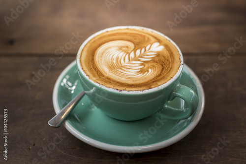 hot cappuccino with latte art on wood background Fototapete