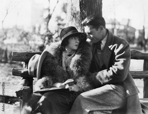 Fotografie, Obraz  Couple in each others arms sitting on a park bench