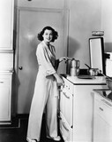 Portrait of woman at stove in kitchen  - 104428516