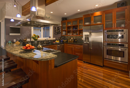 Photo  Contemporary upscale home kitchen interior with wood cabinets and floors, granit