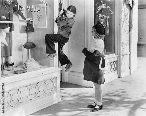 Obrazy vintage   two-girls-on-the-street-with-one-climbing-on-a-display-window