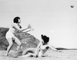 Two women playing with a ball at the beach  - 104437360