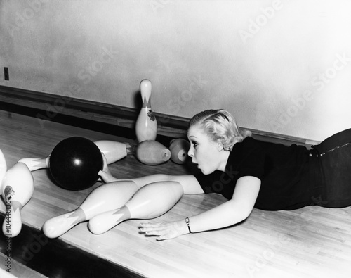 Woman sliding down bowling alley with ball Canvas-taulu