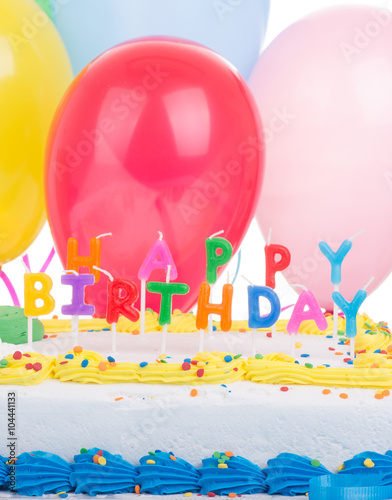 Colorful Birthday Cake Closeup With A Background Of Balloons