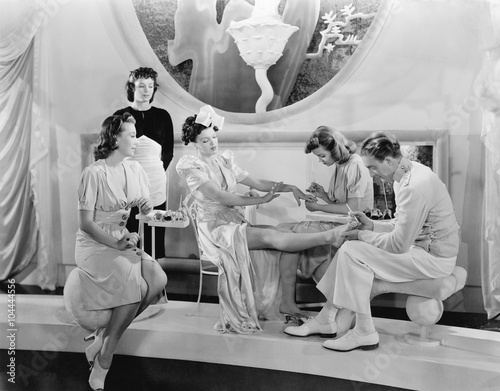 Poster Pedicure Young woman being pampered by three women and a man
