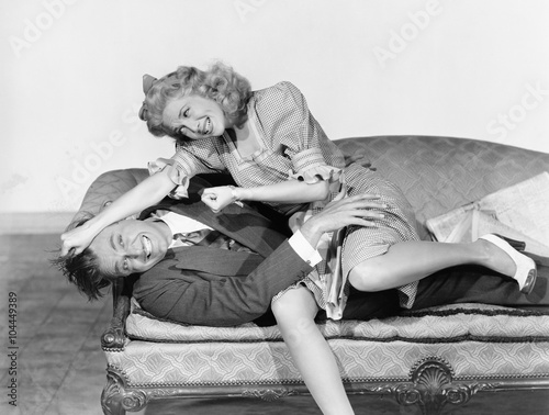 Couple having a playful fight on a couch Canvas Print