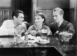 Dwaj mężczyźni i kobieta siedząca przy barze piją piwo - 104449783