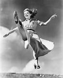 Woman in a flowing dress leaping through the air  - 104450148