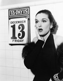 Young woman looking shocked after seeing Friday the 13th on a calendar  - 104452960