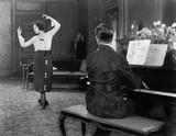 Kobieta tańczy, podczas gdy jej mąż gra na pianinie - 104453174