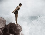 Female swimmer on rock above crashing surf   - 104453914