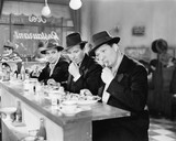 Three men with hats eating at the counter of a diner  - 104459583