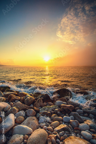 Fotobehang Zwavel geel Tropical colorful sunrise at the stones beach.