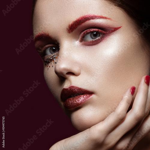 Fotografie, Obraz  Krásná dívka se zářivě červenou módní make-up a krystaly na tváři
