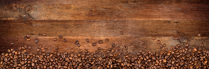 Fototapeta Kawa coffee background with beans on rustic old oak wood