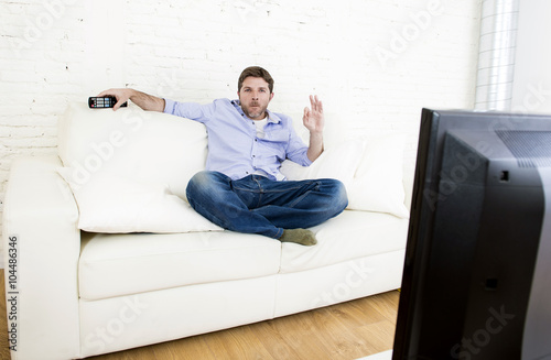 Photo  man watching television at living room sofa with remote control smiling giving