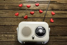 Vintage Radio With Red Hearts On A Rough Wooden Background