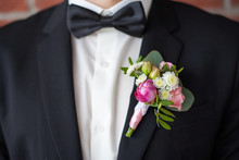 Close Up Of  White And Pink Rose Corsage. Beautiful Boutonniere Pinned On Man In Black Suit, White Shirt And Black Bowtie. Groom Or Graduate.