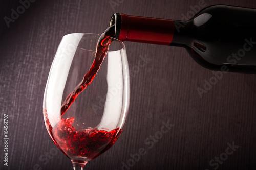 wlewanie-czerwonego-wina-do-kieliszka-na-tle-ciemnej-sciany