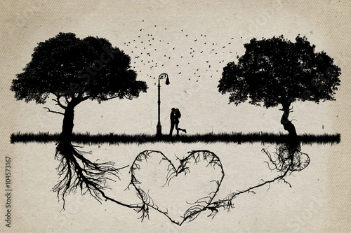 Photo  Two trees in front of each other with underground roots growing together in shape of a heart and a couple hugging in the middle
