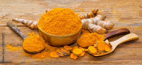 Poster Condiments fresh turmeric roots on wooden table