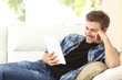 Man reading an ebook or tablet at home