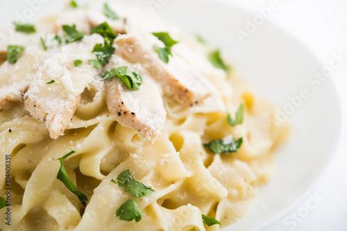 Pasta fettuccine alfredo with chicken, parmesan and parsley on white background close up Wallpaper Mural