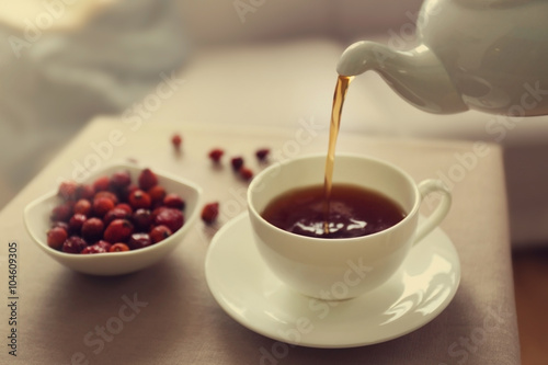 Photo Stands Coffee beans Pouring rose hip tea into cup, home atmosphere