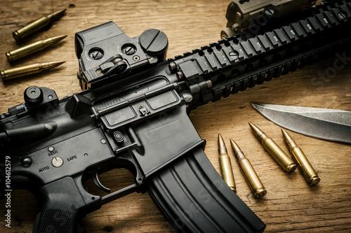 Assault rifle on a wooden table Fototapeta