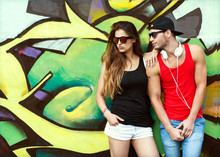 Fashion Couple With Sunglasses Near The Wall Graffiti